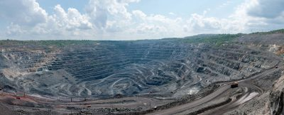 37151779 - panorama of quarry extracting iron ore with heavy trucks, excavators, diggers and locomotives